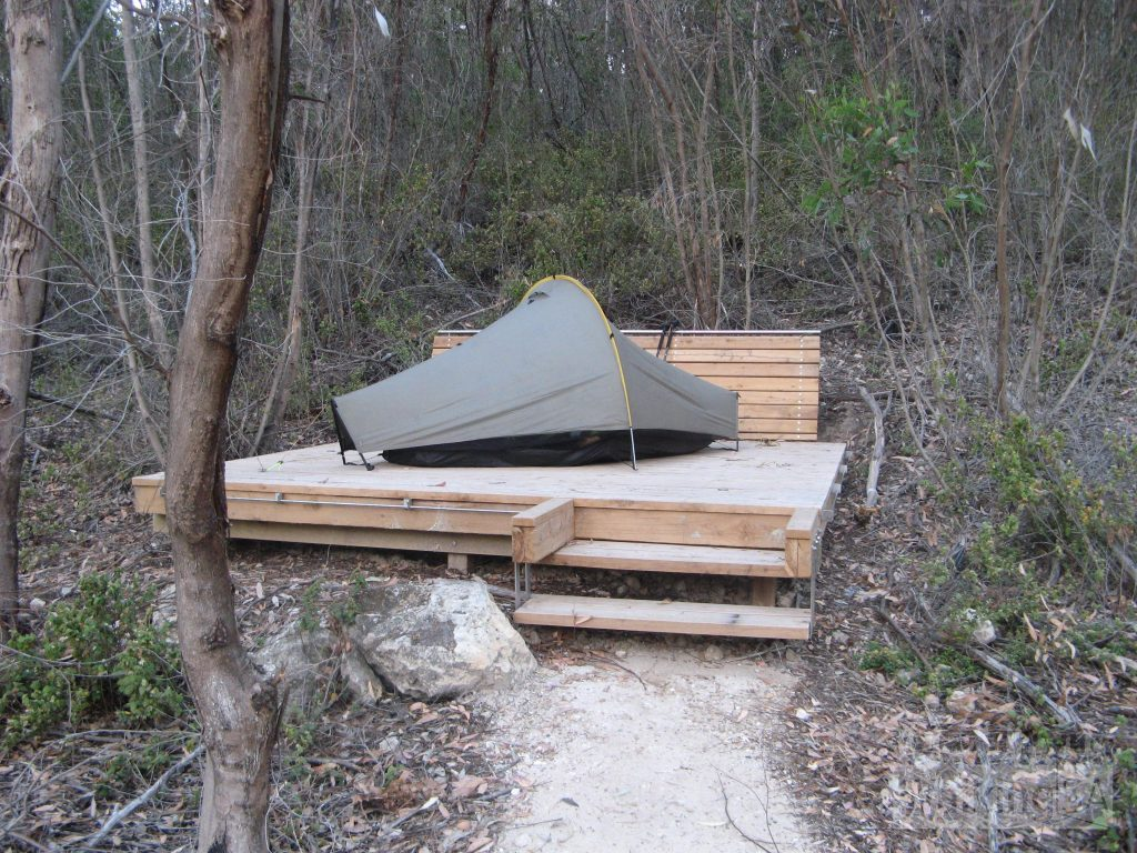 There are timber tent platforms at Cup Gum Campsite, and in the tour group area of Hakea Campsite. Some like this one feature benches (behind tent). There are bars around the sides and pop-up tent pegs to secure your tent to (bring some string or rope)