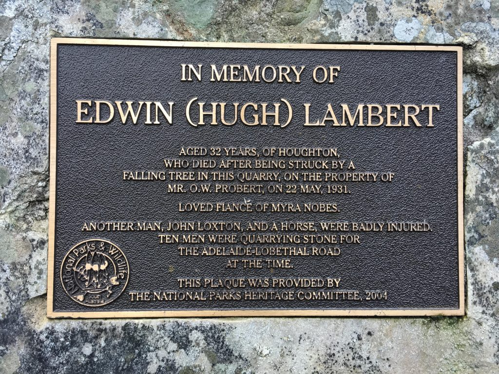 """The plaque in the quarry in the northern end of Kenneth Stirling Conservation Park (Filsell Hill). Plaque states: """"In memory of Edwin (Hugh) Lambert. Aged 32 years, of Houghton, who died after being struck by a falling tree in this quarry, on the property of Mr O.W. Probert, on 22 May, 1931. Loved fiance of Myra Nobes. Another man, John Loxton, and a horse, were badly injured. Ten men were quarrying stone for the Adelaide to Lobethal Road at the time. This plaque was provided by the National Parks Heritagte Committee, 2004."""""""