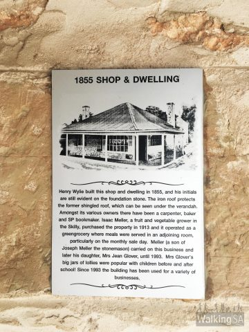 Historic buildings throughout Auburn have plaques on them which correlate to the heritage walk brochure 'A Walk with History at Auburn'. This plaque reads: Henry Wylie built this shop and dwelling in 1855, and his initials are still evident on the foundation stone. The iron roon protects the former shingled roof, which can be seen underneath the verandah. Amongst the various owners there have been a vegetable grower in the Skilly, purchased the property in 1913 and it operated as a greengrocery where meals were served in an adjoining room, particularly on the monthly sale day. Meller (a son of Joseph Meller the stonemason) carried on business and later his daughter, Mrs Jean Glover, until 1993. Mrs Glover's big jars of lollies were popular with children before and after school! Since 1993 the building has been used for a variety of businesses.