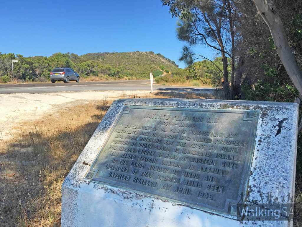 "The plaque with Prospect Hill beyond. The plaque reads: ""Matthew Flinders R.N. (1774 - 1814). Commander of H.M. Sloop ""Investigator"" discovered and on 4 April 1802 named Prospect HIll from which he was the first to sight portion of south coast of Kangaroo Island. The hidden lagoon at head of Easter Cove was named Pelican Laroon on account of the large number of birds and skeletons of that species being seing. Unveiled Pioneers Day April 1948."""