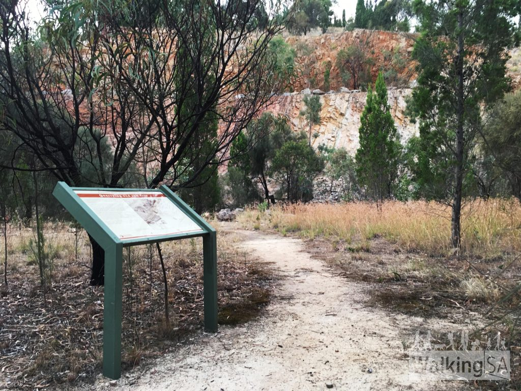 One of the former quarries along the Geological Hike, with an interpretive sign