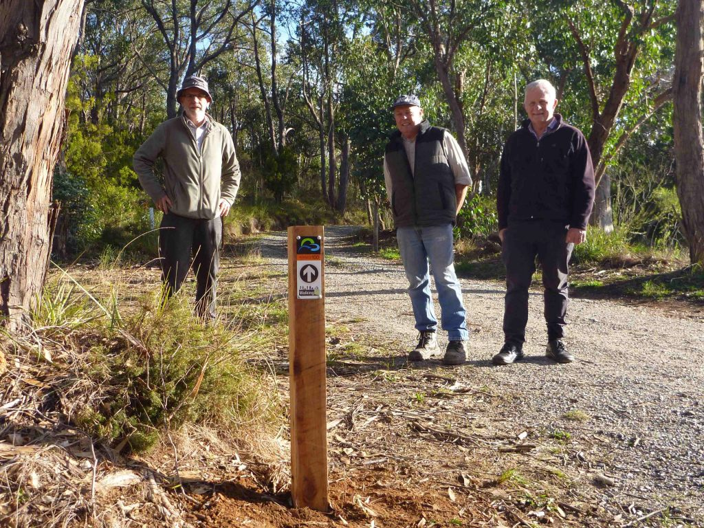 Jim Mclean, trail visionary, with John Potter, from the Friends of the Heysen Trail, and helper Bill Gehling having installed the first Adelaide 100 post.
