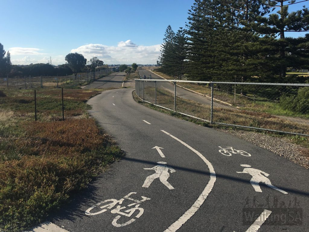 The western end of the trail begins at the junction of Tapleys Hill Road and Warren Avenue/ James Melrose Road. There is a short section in the background of the photo along the former Tapleys Hill Road (it was diverted in 1998 to allow for the runway to be extended), however the dedicated path begins soon after leaving the former road