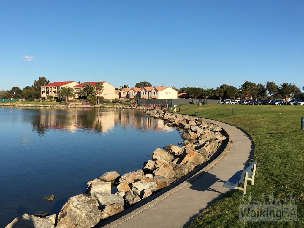 Walking around the lake at West Lakes, past a playground and toilets at Inlet Reserve
