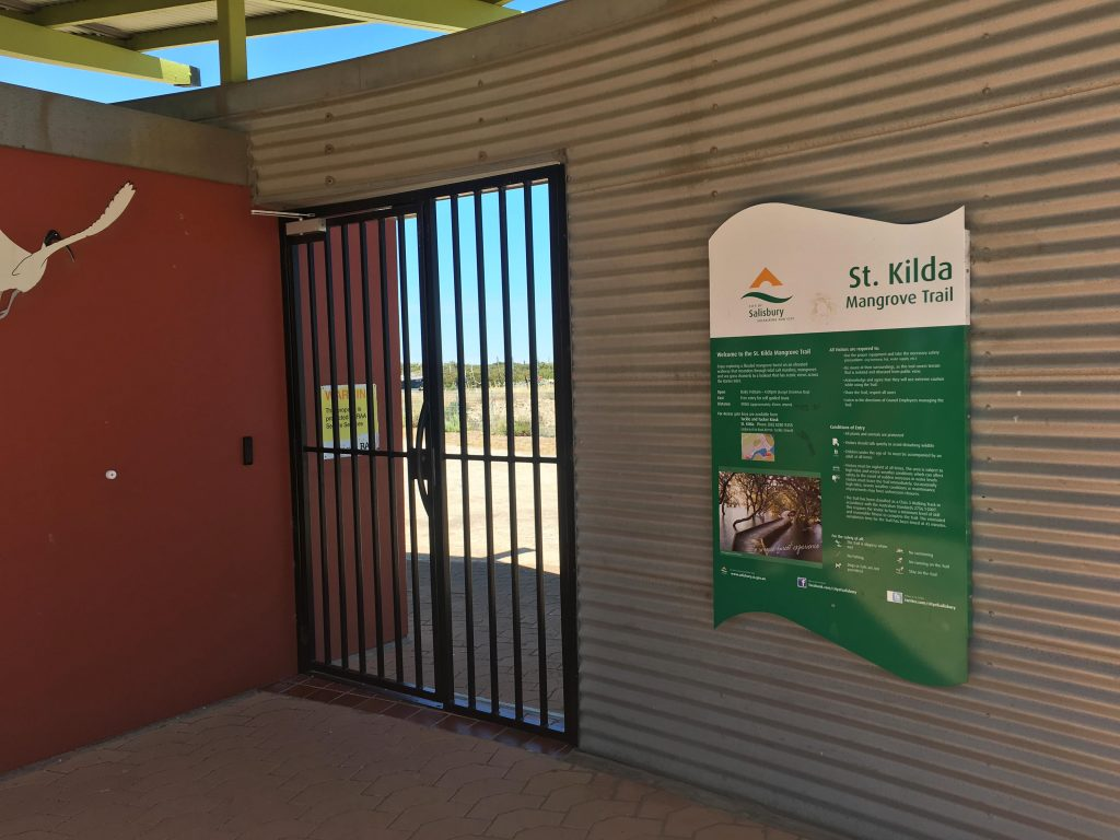 "Entrance gate to the St Kilda Mangrove Trail. The walk is open daily between 9am and 4pm (except Christmas Day). Entry is free, but you need to obtain an Access Gate Key from the kiosk (<a href=""https://www.google.com.au/maps/place/St+Kilda+Tackle+'N'+Tucker/@-34.7437931,138.534443,19z/data=!4m13!1m7!3m6!1s0x6ab0ba2128b07923:0x31bbda9fed637e91!2sSt+Kilda+SA+5110!3b1!8m2!3d-34.7382025!4d138.534511!3m4!1s0x6ab0ba20e7feffc3:0x66f44de6192a0968!8m2!3d-34.7439207!4d138.5348182?hl=en"">Tackle & Tucker</a>) near the Adventure Playground."