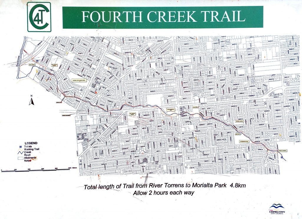 Map of the Fourth Creek Trail (photo of an old sign). The walking trail is marked in yellow/orange.