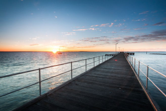 """Cowell jetty. Built in 1882 the Government was not interested in upgrading the facilities, so on the formation of the District Council of Franklin Harbour in 1888, tolls on cargo were introduced to finance further upgrades. In 1901 the sea end of the jetty was widened by 200feet and extended by 300 feet in 1904. The jetty became a very important shipping port. From 1908 the Steam Ship """"Rupara"""" with her magnificently appointed public rooms and accommodation for passengers, called at Pt Lincoln, Tumby Bay, Cowell & Wallaroo, providing a five day cruise called """"The Gulf Trip"""". The last passenger vessel to call at Cowell was the """"Morialta"""" in the mid 1950's."""