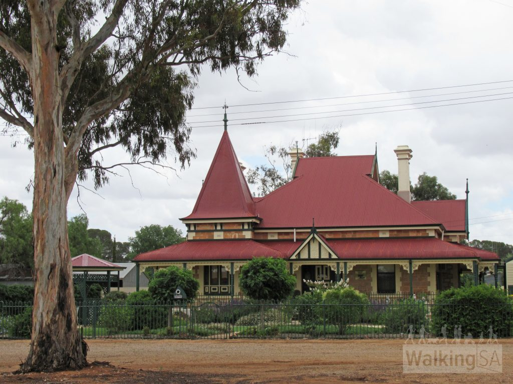 """No 19 Eyre Road, Cystral Brook, on the Historic Homes town walk. The house is a beautiful example of Queen Anne architecture, the only one in Crystal Brook. This adaption of 19th century English Revival concept was popular between 1905-1918, incorporating the turret top. Turned pendant drops are used on the main roof. Note this home has a """"louvre roof"""". Venting at the sides of the apex of the roof allows hot air to escape while being replaced with cooler air via the eaves. This stately home was built in 1902 for Wandearah farmer, Oliver Adcock, who carted all the local stone needed for its construction. Mr Smerden, a builder from Port Pirie, built the residence for £800 in 1902."""