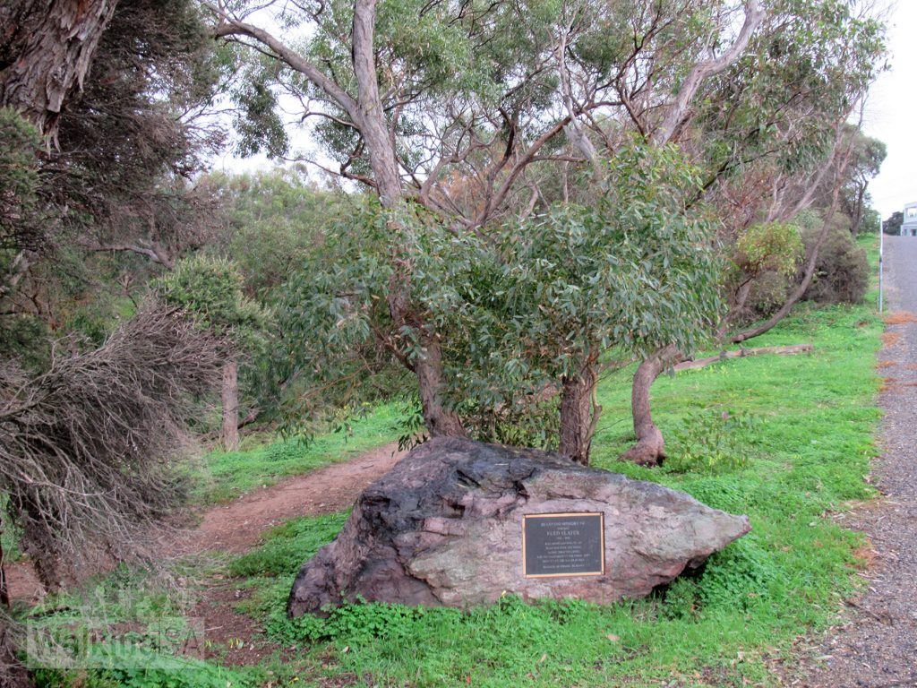 """A plaque on Hunter Road, near #8, dedicated to the volunteer who planted over 2,000 trees along Christies Creek. The plaque reads: """"In loving memory of our dad, Fred Slater. 1931 - 2002. Who spent eighteen years planting over 2,000 trees along Christies Creek for the enjoyment of the community. Erected by the Slater Family. `Be good, be strong, be happy`"""""""