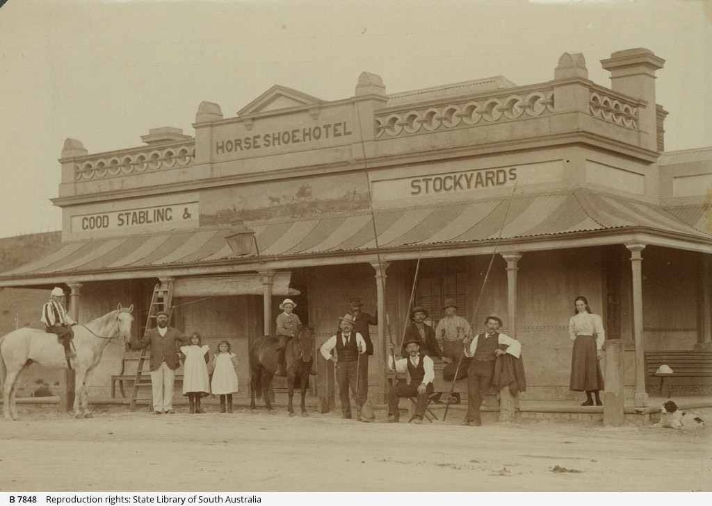 """The Horseshoe Hotel, pictured in 1899, with probably John Charles Dungey, the proprietor from 1887-1889 and again from 1893-1914, with the girls likely to be his daughters. Note the fishing rods the other men are holding, the inn was known for organising fishing parties on the tidal river. Photo <a href=""""https://collections.slsa.sa.gov.au/resource/B+7848"""">B 7848 State Library of South Australia</a>."""
