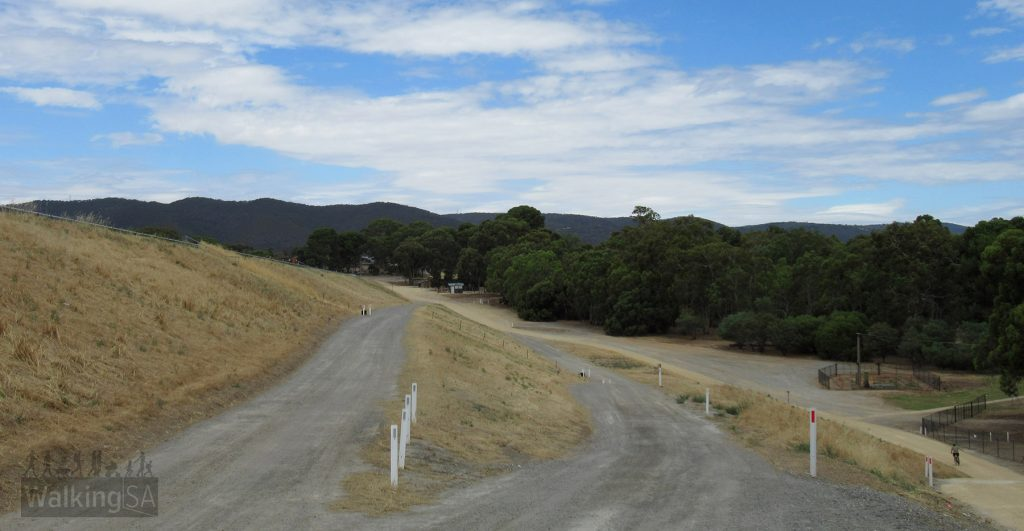 From the far end of the dam wall, looking south back to the Lyons Road carpark. There are several parallel trail options beneath the dam wall.